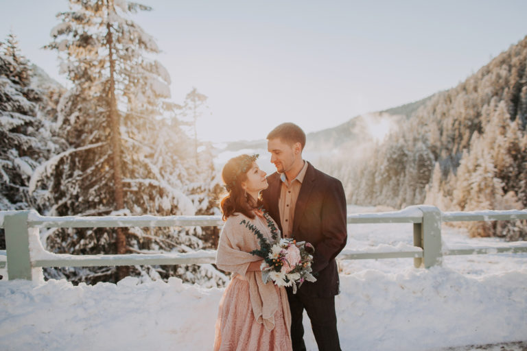 Elopement at Mount Rainier in winter at sunset time. Golden hours and snow in Rocky Mountains. Blush pink wedding dress in snow