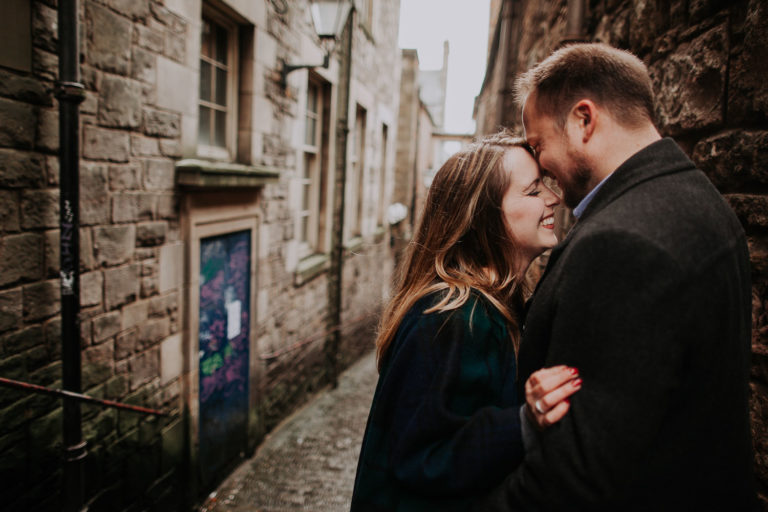 Moody destination spring engagement session in Old Town of Edinburgh, Scotland. Rainy engagement near Edinburgh Castle by destination photographer