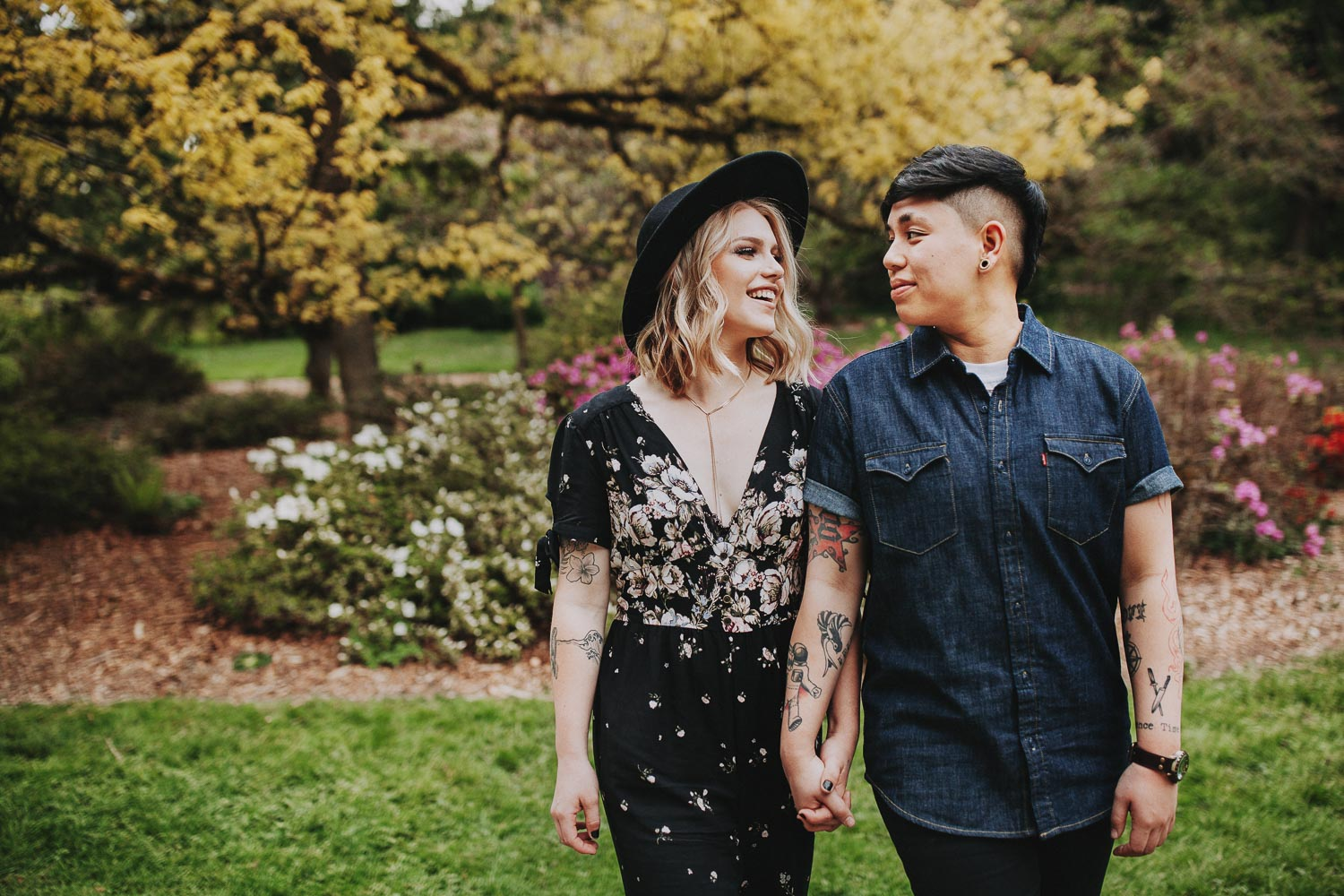 Beautiful same sex couple in spring engagement session with cherry blossom in Seattle Arboretum